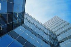 Kristallbürogebäude, die einen blauen Himmel reflektieren Stockfotos