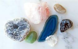 Kristalle und Edelsteine auf Marmorhintergrund Lizenzfreies Stockfoto