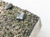 kristaller av Epidote på stenslut upp på vit Arkivfoto