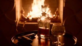 Kristallkaraffe mit Whisky und das Glas gegenüber von dem Kamin auf Vorabend Pistole auf der Tabelle stock footage