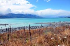 Kristallklar blå sjö med mountians i avståndet Arkivfoton