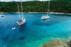 Kristallklart genomskinligt blått vatten för turkoskrickamedelhav av den Foki Fiskardo stranden med någon vit yacht in Arkivfoton