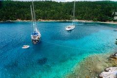 Kristallklart genomskinligt blått vatten för turkoskrickamedelhav av den Foki Fiskardo stranden med någon vit yacht in Arkivbild