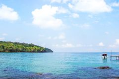 Kristallklart vatten för havsikt från Haad Sai Daeng Beach, som har träbron för överföringsturister på den Koh Kood ön, Trat royaltyfri fotografi