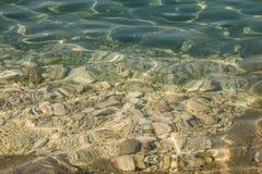Kristallklart vatten med genomskinligt yttersidasken under den ljusa sommarsolen Färgrika undervattens- stenar Solstrållek Arkivbild