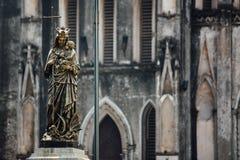 Kristen bronsstaty av ett hållande barn för kvinna tränger igenom arkivbild