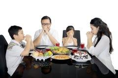 Kristen familj som ber för att ha matställen på studio royaltyfria foton