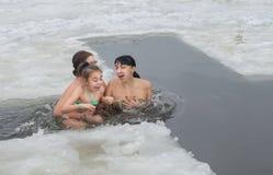 Kristen ferie av epiphanyen Flickan barn, badade i floden i vintern, i hålet med vuxna människor Arkivfoton