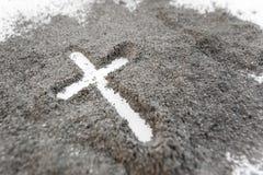 Kristen kors- eller korsteckning i aska, damm eller sand som symbol av religionen, offer, redemtion, Jesus Christ, aska onsdag arkivbilder