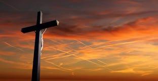 Kristen korsar över solnedgångbakgrund arkivbilder