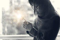 Kristen kvinna med korset i händer som ber hopp och dyrkan på regndroppebakgrunden abstrakt lighting Nattvardterapibles arkivfoto