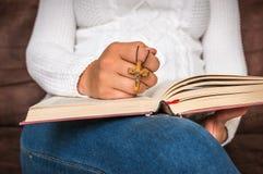 Kristen kvinna med träarg läsning en helig bibel arkivfoto