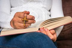 Kristen kvinna med träarg läsning en helig bibel arkivfoton