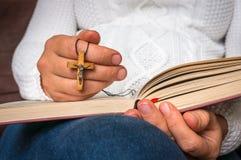 Kristen kvinna med träarg läsning en helig bibel royaltyfri fotografi