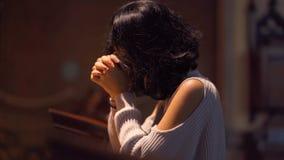 Kristen kvinna som ber till GUDEN i kyrkan lager videofilmer