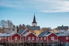 Kristen kyrka på rött fiskeläge på kustlinjen royaltyfria foton