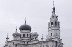 Kristen ortodox vit kyrka med silver och gråa kupoler med guld- kors Lugna grå himmel över royaltyfri bild