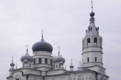 Kristen ortodox vit kyrka med silver och gråa kupoler med guld- kors Lugna grå himmel över arkivbilder