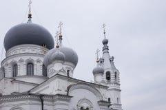 Kristen ortodox vit kyrka med silver och gråa kupoler med guld- kors Lugna grå himmel över royaltyfria bilder
