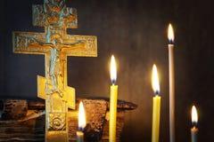Kristen stilleben med forntida metallkorsfästelse och stearinljus Arkivfoton