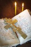 Kristen stilleben med gammal korsfästelse och den forntida boken arkivfoto