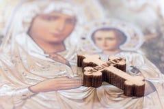 Kristen välsignat träkors och helig moder i bakgrund royaltyfri bild