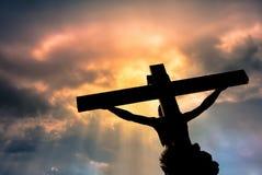 Kristenkors med den Jesus Christ statyn över stormiga moln Arkivbilder