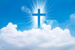 Kristenkorset verkar ljust i himlen arkivfoton