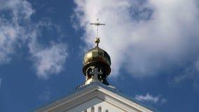 Kristet kors på kupolen av kyrkan mot en fuktig klar himmel lager videofilmer