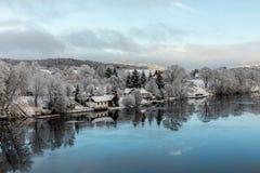 Kristiansand Norge - Januari 17, 2018: Scenisk sikt av den Tovdal floden på Tveit, med hus vid flodstranden Vinter Royaltyfri Bild