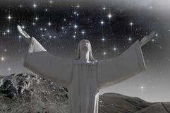 Kristus med öppna armar under stjärnklar himmel Arkivbild