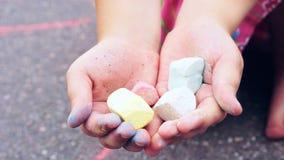 Krita i barn` s räcker närbild Barnet som tecknar en krita på asfalt Barnteckningsmålningar på asfaltbegrepp arkivfoton