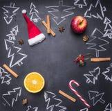 Kritabräde med den målade julpynt, julgranar, godisen, koppar och ingredienser för funderat vin, ram, utrymme f Royaltyfri Fotografi