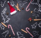 Kritabräde med målat julpynt, julgranar, godis, koppar, ingredienser för funderat vin, belagd med tegel ram, utrymme f royaltyfri bild
