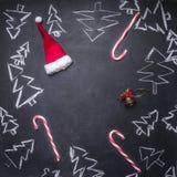 kritabrädet målade julpynt, julgranar, godisen, koppar och ingredienser för funderat vin, den belade med tegel ramen, utrymme f arkivfoton