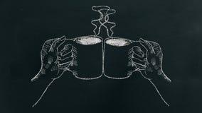 Kritahand som drar två händer som rymmer kaffekoppen med ånga och jubel på svart bräde arkivbilder