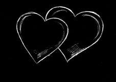 Kritahjärtor på en svart bakgrund Arkivfoto
