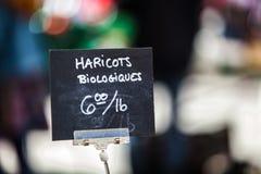 Kritatecken som säljer organiska bönor under namnharicotsbiologiquesna arkivbild