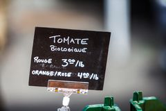 Kritatecken som säljer organiska röda, orange och rosa tomater royaltyfri bild