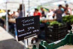Kritatecken som säljer organiska röda, orange och rosa tomater arkivbilder