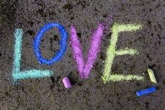 Kritateckning på asfalt: Färgrikt ord FÖRÄLSKELSE Arkivfoto