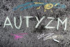 Kritateckning: Polskt ord AUTISM och stycken av krita arkivfoton
