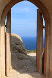 Door to the Sea. View at entrance wooden gate of the fortress of the Maltese period near Kritinia on a sunny day. Rhodes, Greece Stock Images