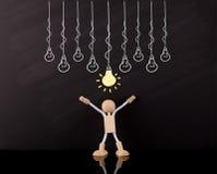 Kritisches denkendes Fähigkeits-Konzept, hölzerne Stock-Zahl Arme oben, große gelbe Glühlampeskizze, auf einer Tafel stockfoto