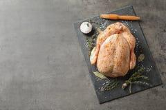 Kritisera plattan med den rå kryddade kalkon på grå bakgrund, bästa sikt royaltyfria bilder