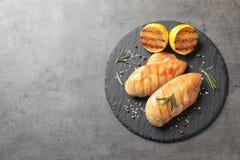 Kritisera plattan med den stekt kycklingbröst och citronen på grå bakgrund, bästa sikt royaltyfri fotografi