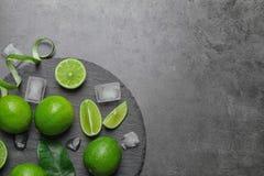 Kritisera plattan med nya mogna limefrukter och iskuber Fotografering för Bildbyråer