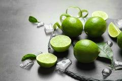 Kritisera plattan med nya mogna limefrukter och iskuber Arkivfoton