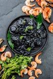 Kritiserar den svarta raviolit för italienare med havs- räkor och krabbor på den svarta plattan, grå färgsten bakgrund Top beskåd Arkivbilder