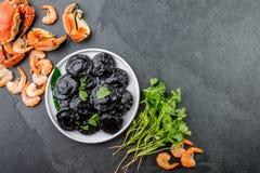 Kritiserar den svarta raviolit för italienare med havs- räkor och krabbor på den svarta plattan, grå färgsten bakgrund Top beskåd Royaltyfri Bild